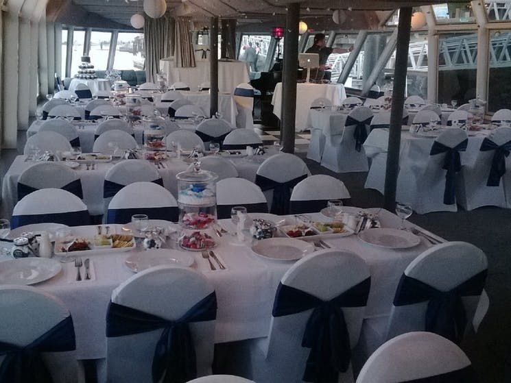 """Chairs and tables set up for a wedding onboard 'The Princess""""."""