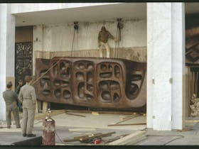 Installing the Tom Bass lintel sculpture over the main entrance of the National Library, 1969