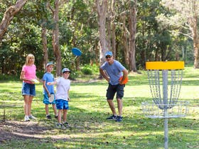 Family watching child play Disc Golf