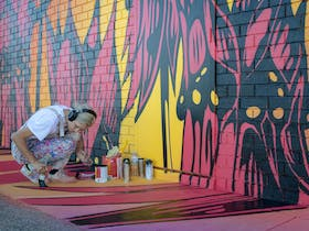 George Rose applying some finishing touches to her super colourful Sturt Desert Pea Mural