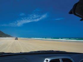View through car window of driving along sandy beach towards headland, Cooloola.