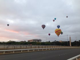 Ten hot air balloons float over the National Library