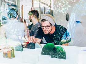 Man looking at glass art objects