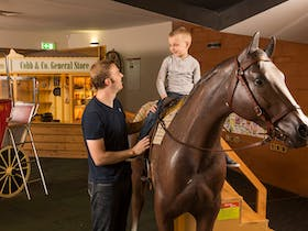 Father supporting son on replica sized horse