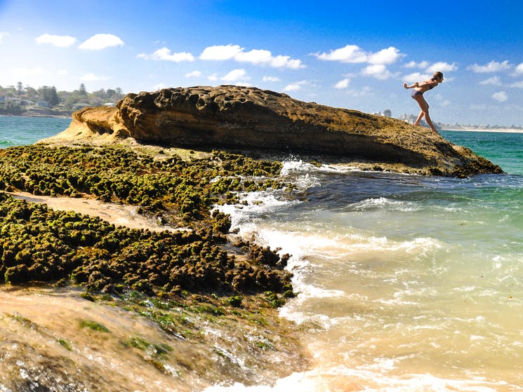 Girl diving into ocean waters from rocks
