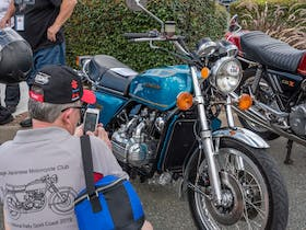 An impeccably restored Honda GL1000 being admired and photographed.