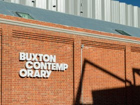 Exterior brick wall with white Buxton Contemporary signage