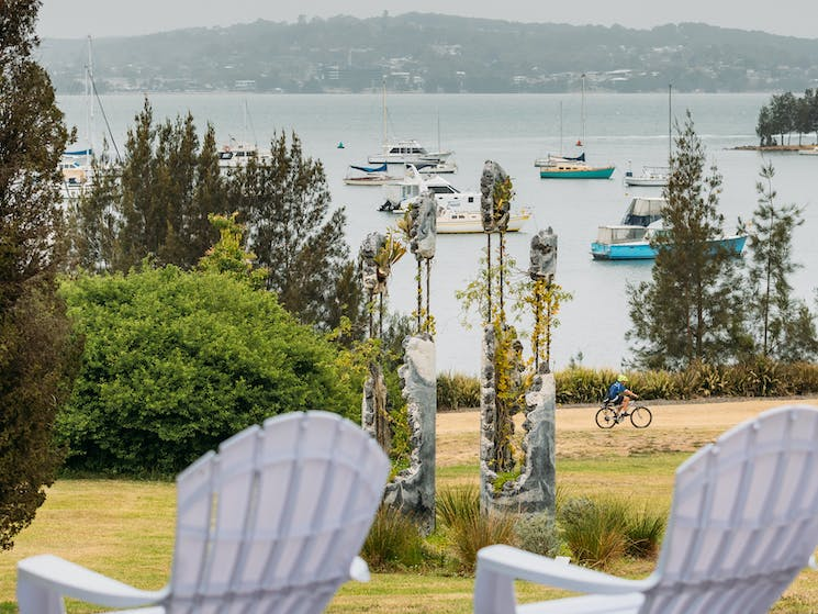 Two white deck chairs with Lake Macquarie and Jamie North's sculpture in the background