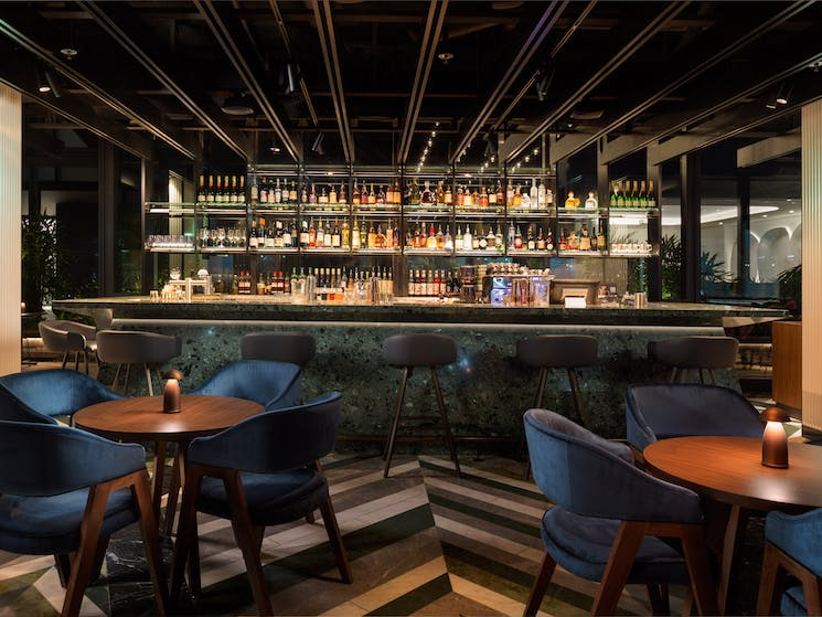 Solander Bar offers bespoke botanical-inspired cocktails served from the emerald green terrazzo bar.