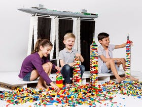 Three kids creating Lego towers