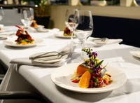 Plated salmon served with vegetables displayed on a table with white linen tablecloth