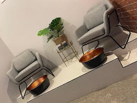 two grey chairs with bowls underneath for pedicures