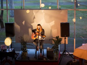 Woman playing a guitar on an informal stage in front of a large window