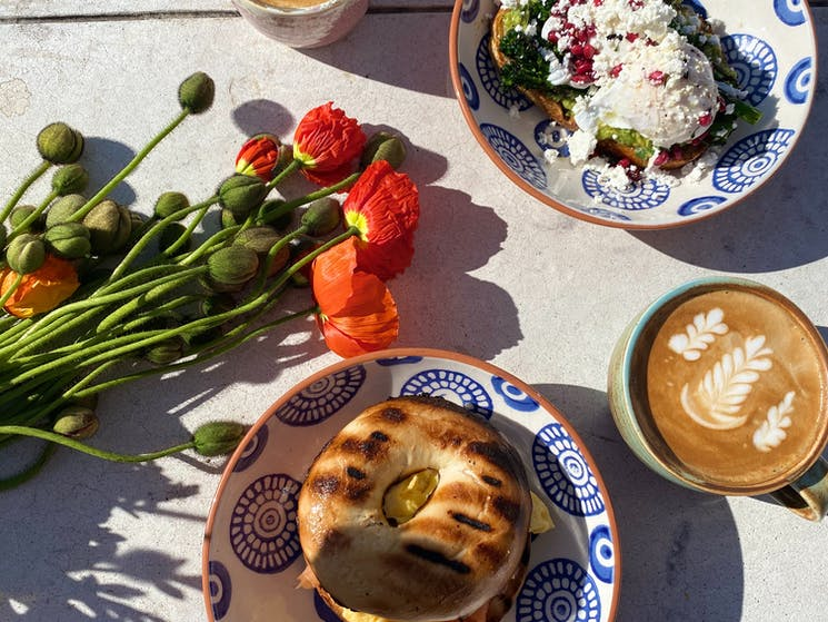 A shot showing a breakfast or brunch meal with coffee and fresh bunch of poppies
