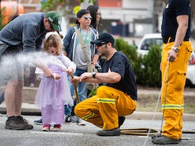 firefighter spraying hose with young child